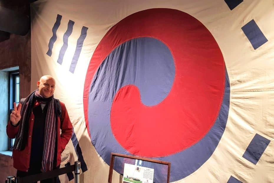 Joel, an expat in Korea, standing by an old Korean flag