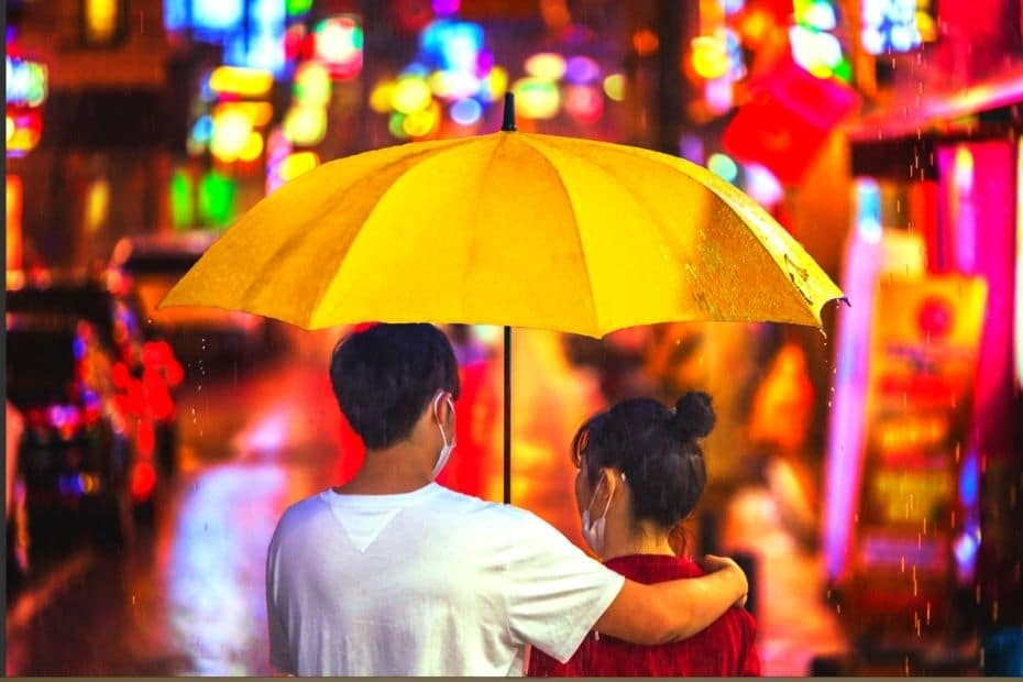 Korean couple walking together in the rain