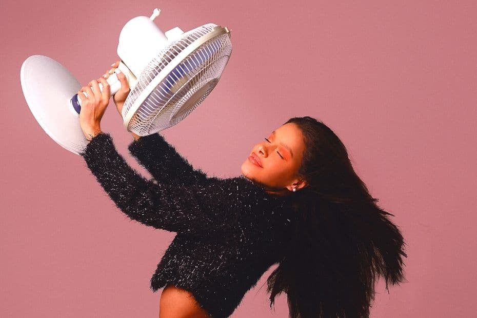Woman keeping cool with a fan
