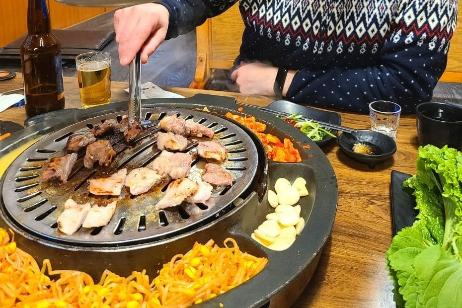 Eating Korean BBQ, a traditional Korean dish